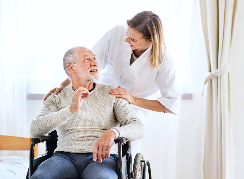 caregiver and a senior man looking at each other