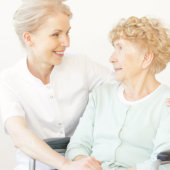 caregiver and a senior woman looking at each other