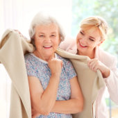 caregiver placing blanket to a senior woman