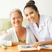 caregiver and a senior woman smiling
